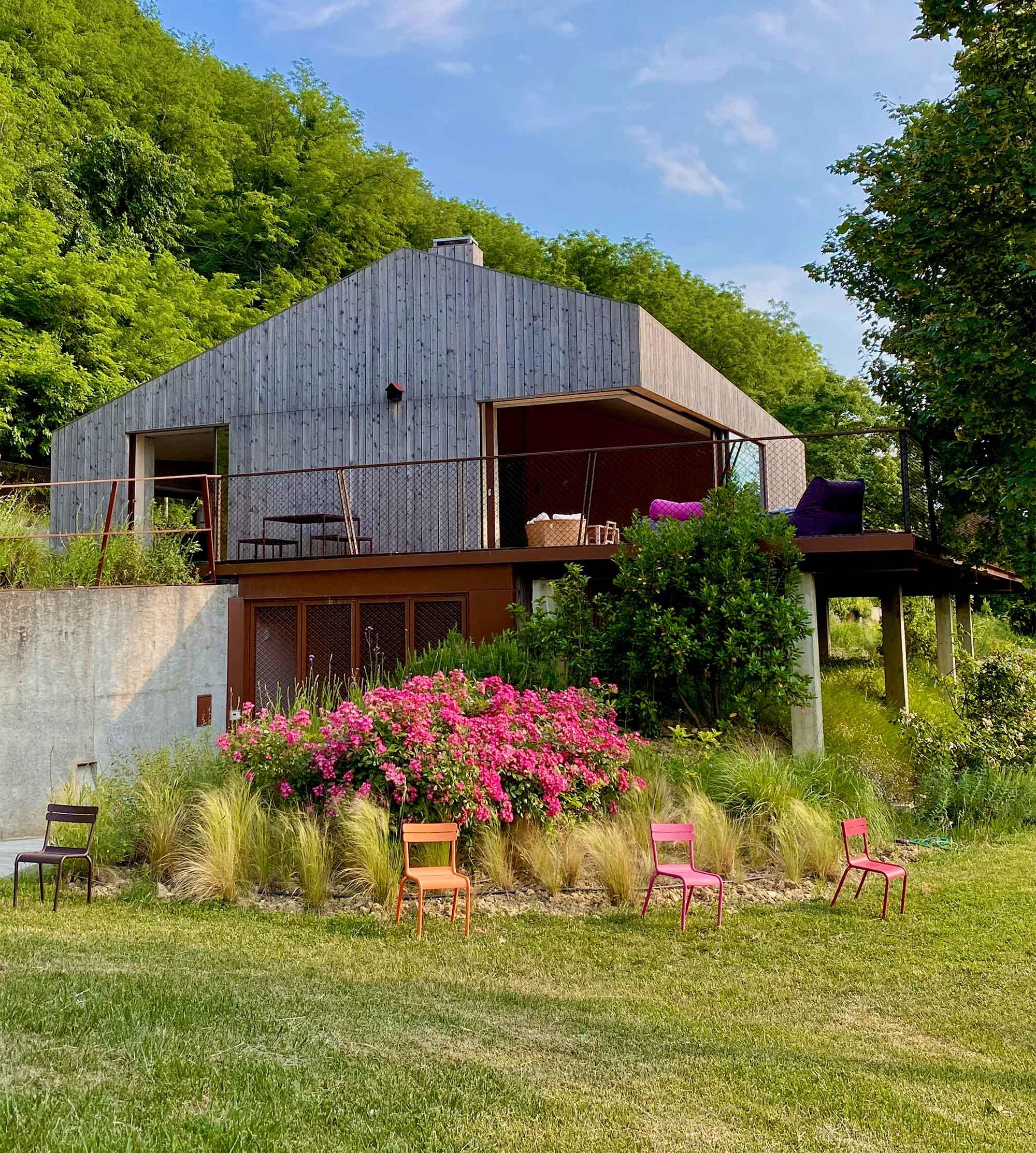 Das hübsche Grün umgibt das einzigartige Holzhaus La Mugletta