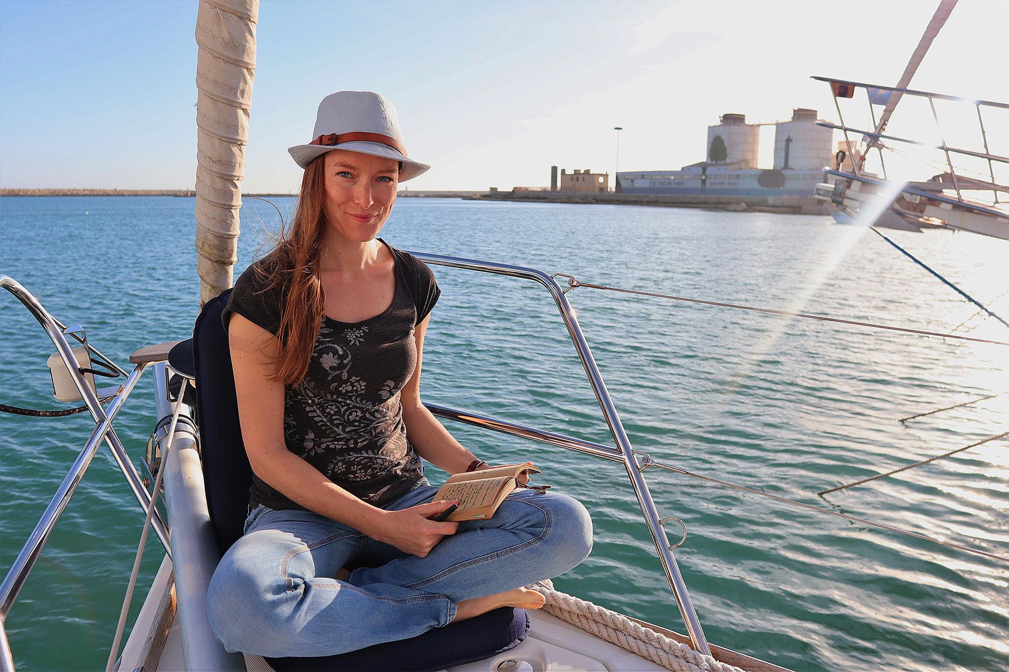 Ina schreibt auf dem Segelboot in ihr Notizbuch